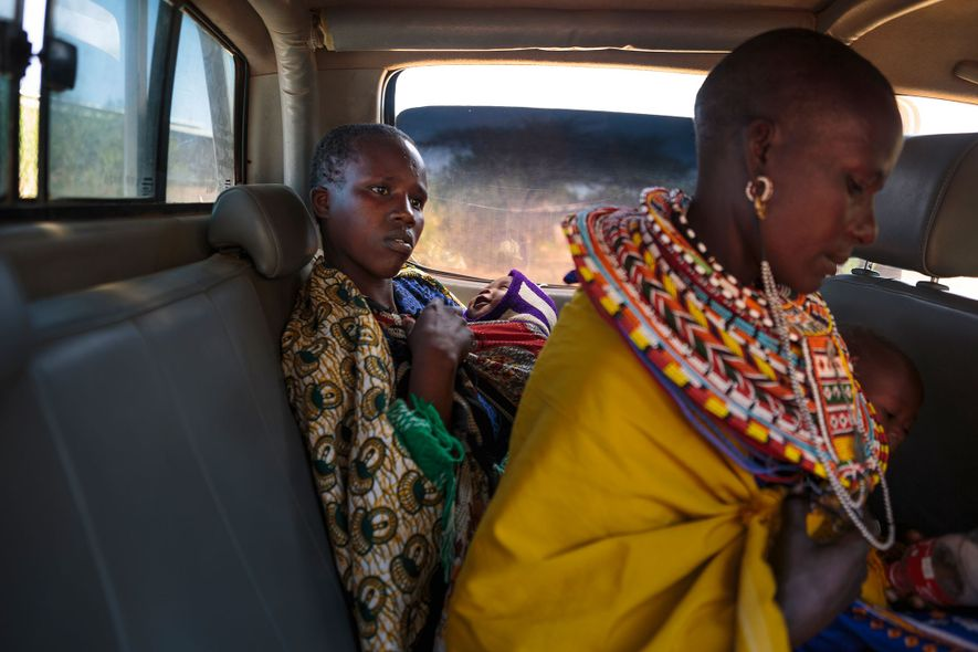 Dos madres jóvenes sostienen a sus bebés en el asiento de atrás de una camioneta de ...