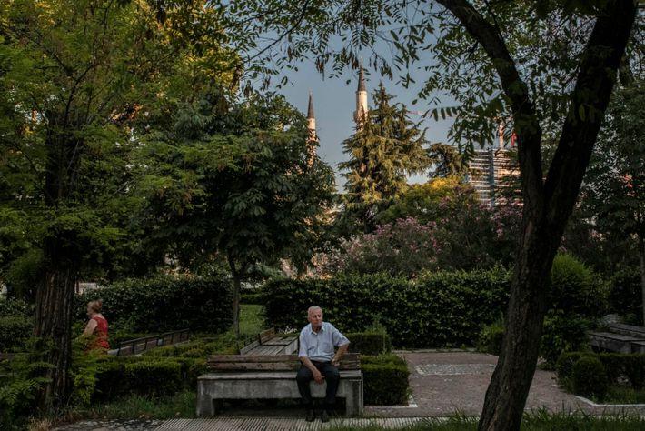 Un hombre sentado en un parque del centro de Tirana