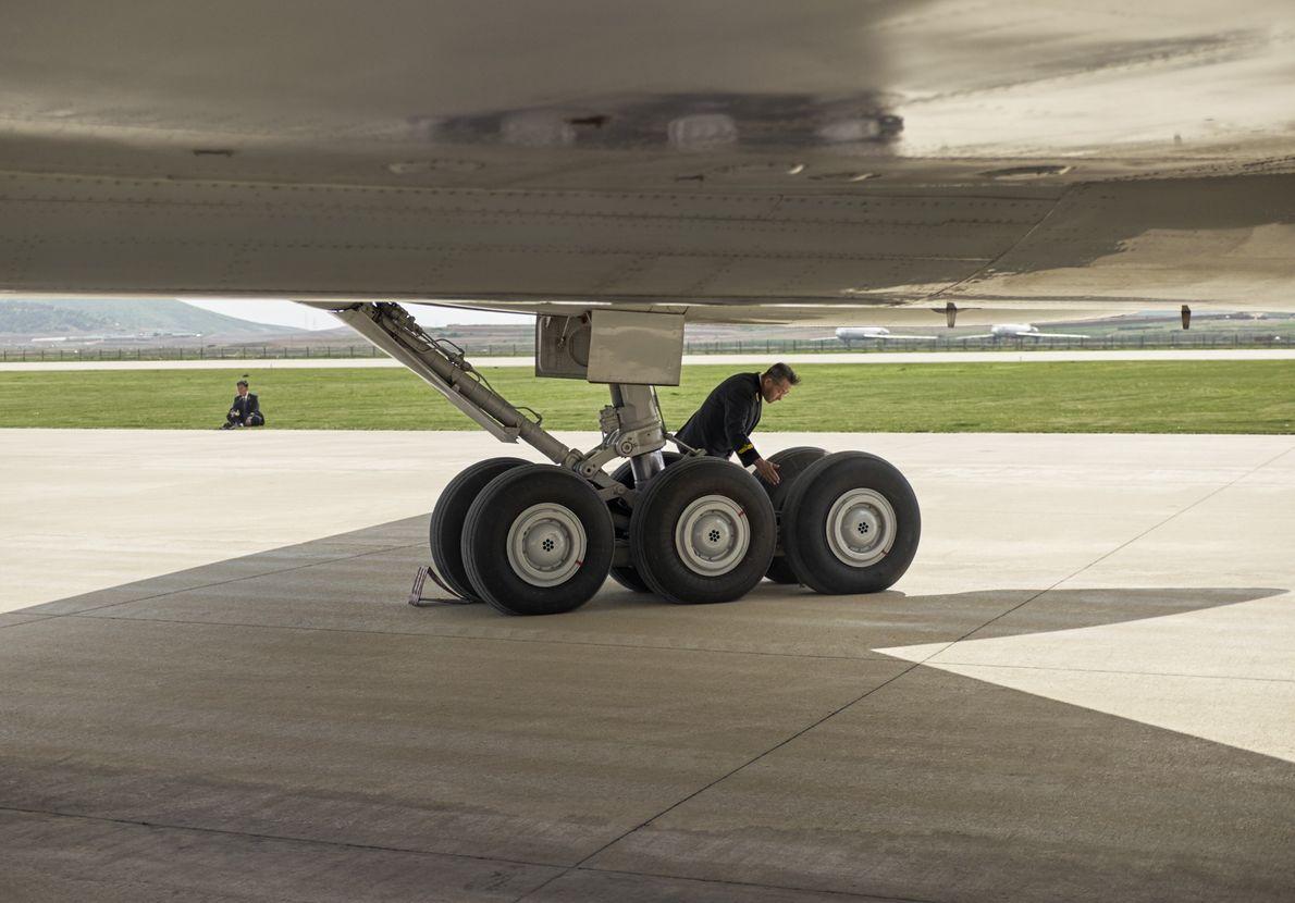 Un piloto inspecciona las ruedas