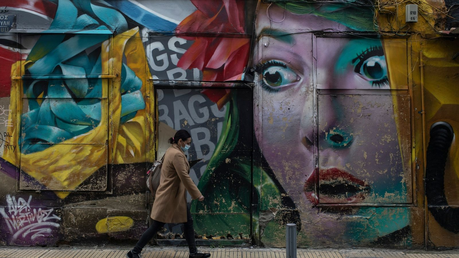 Una mujer con mascarilla camina frente a un mural