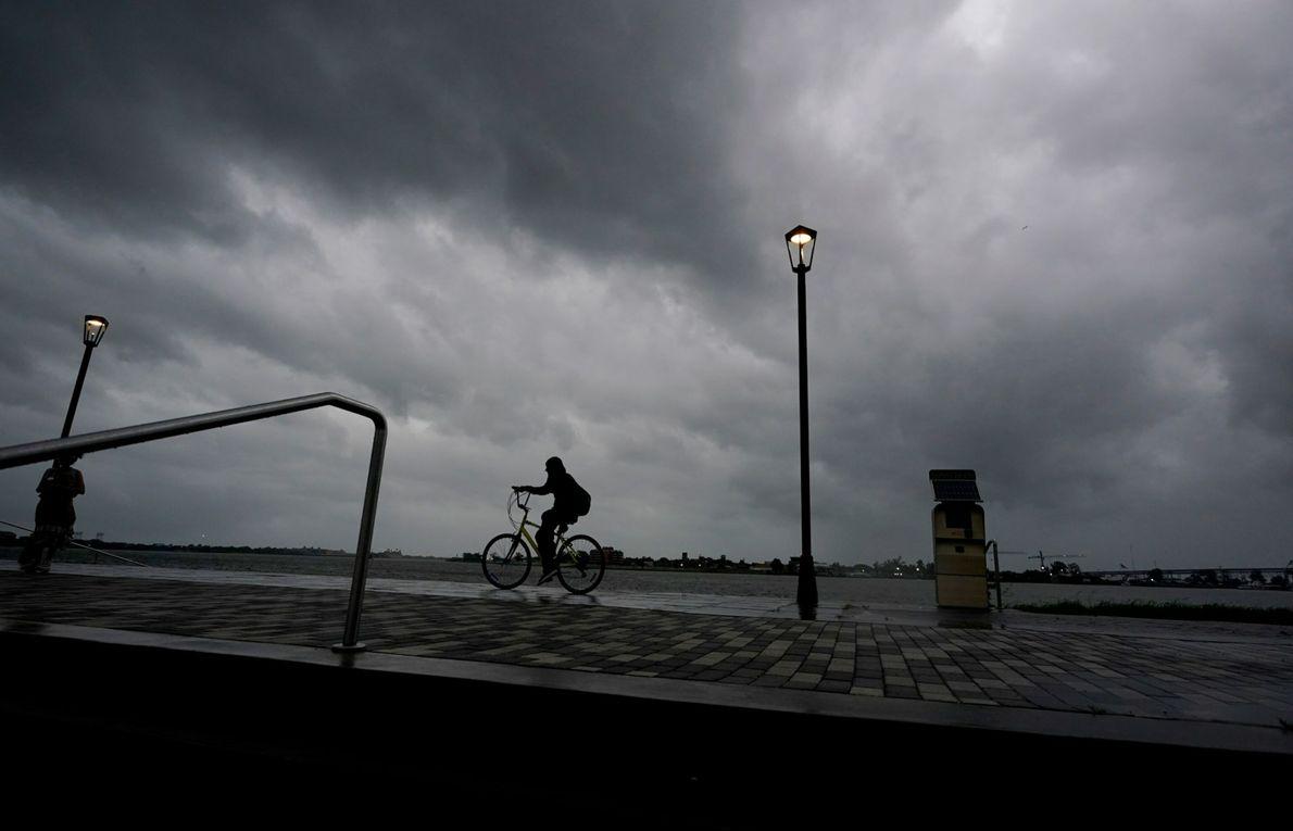 Un hombre va en bici junto al río Mississippi cerca del Barrio Francés a medida que ...