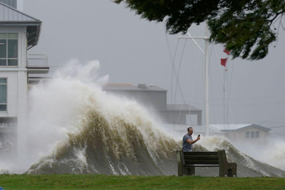 Un hombre hace fotos con su móvil de las enormes olas en la costa del lago Pontchartrain, ...