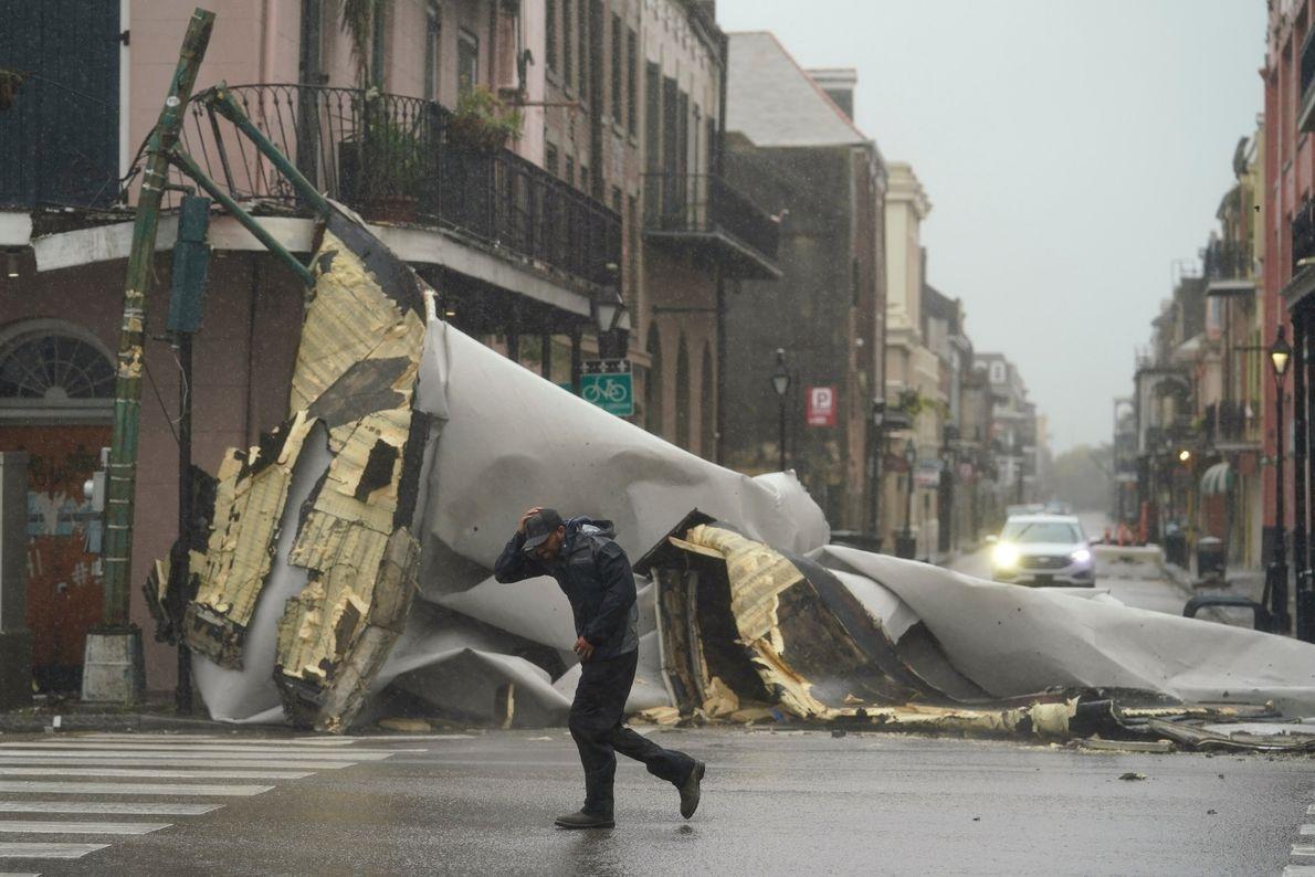 Un hombre pasa por delante del techo de un edificio destruido por el huracán Ida en ...