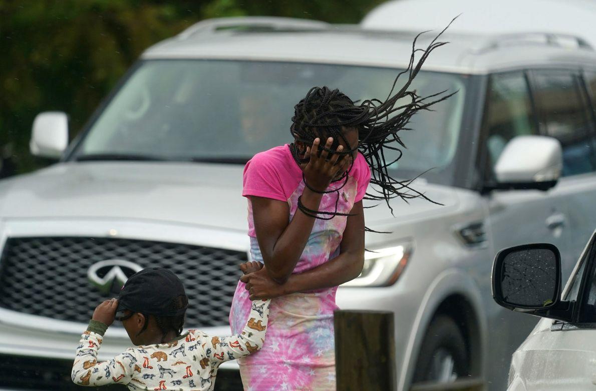 Una niña tapa su rostro del viento y la lluvia producidos por el huracán Ida en ...