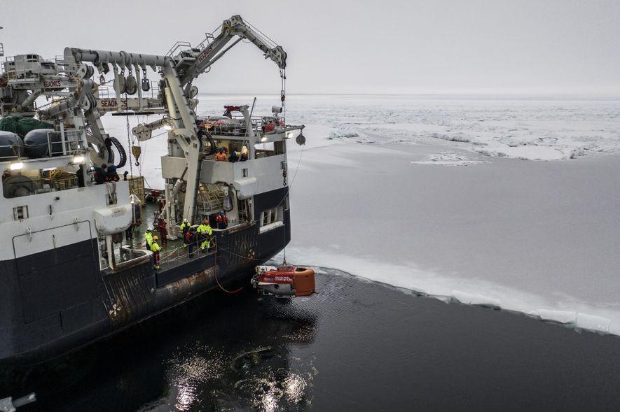 El vehículo naranja Nereid Under Ice desciende a las aguas árticas desde el Kronprins Haakon. El ...