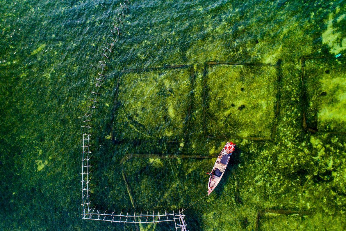 Un pequeño barco permanece amarrado en la costa de una pequeña aldea pesquera en Phú Quốc, …