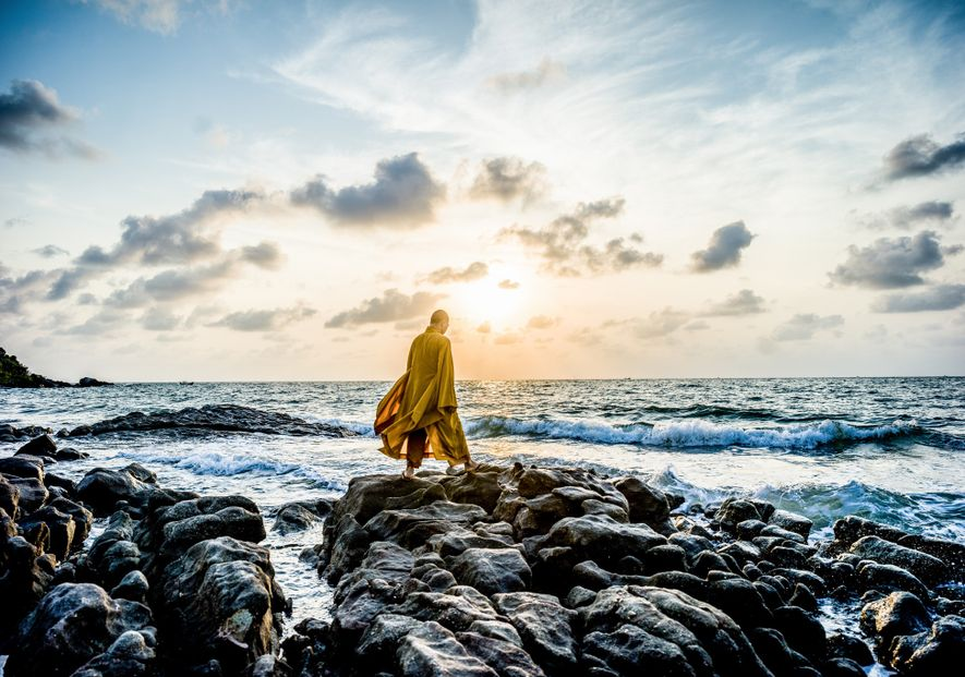 Un monje budista medita al amanecer en la orilla.