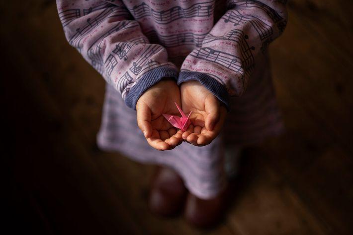 Niño con grulla de papel