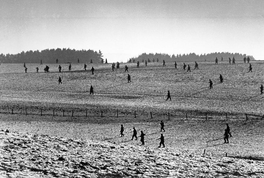 Los soldados estadounidenses, que se recuperan del ataque del 16 de diciembre, avanzan por un campo ...