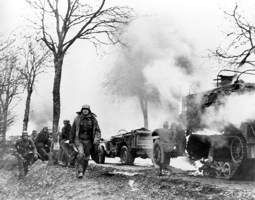 Los soldados de infantería alemanes pasan frente a vehículos estadounidenses quemados durante la batalla de las ...