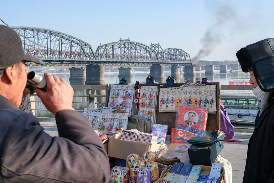 Un hombre examina productos en venta en un puesto turístico en Dandong, cerca del Puente de …