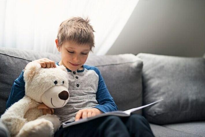 Un niño lee con su osito de peluche