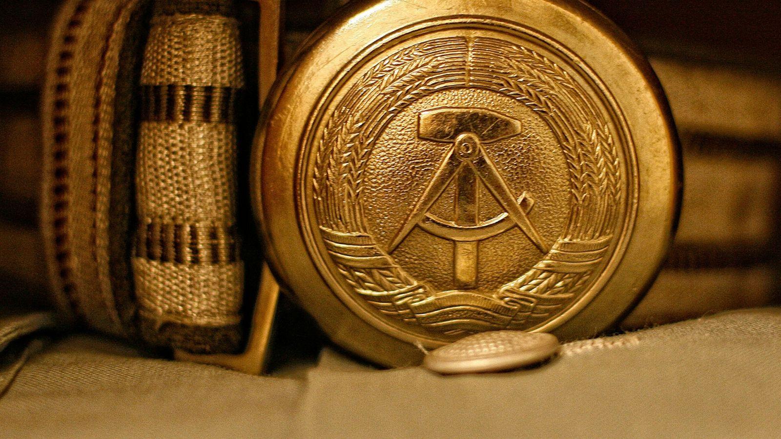 Emblema nacional de la extinta RDA grabado en la hebilla de un cinturón de un uniforme ...