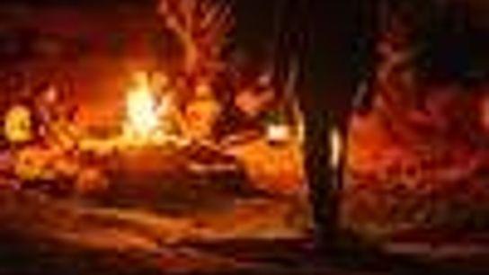 Foto de personas alrededor de una fogata, de noche.