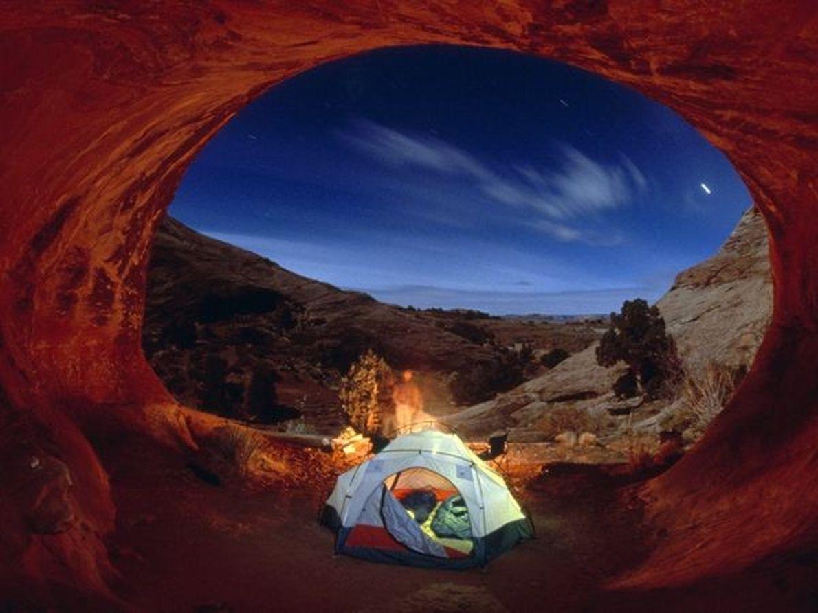 Imagen de personas acampadas bajo las estrellas en el Parque Nacional Arches, Utah.
