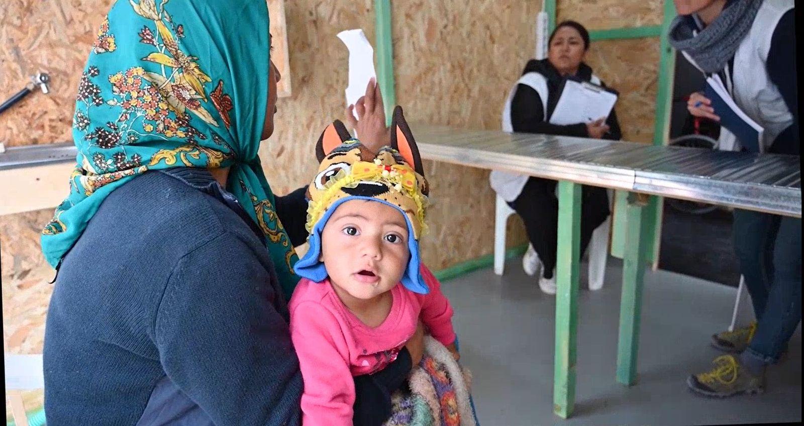 Una mujer acude con su hija a un puesto de atención en el campo de Moria, ...