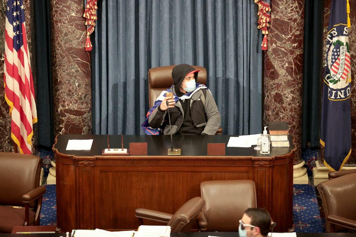 Un insurgente sentado en la mesa de la Cámara del Senado