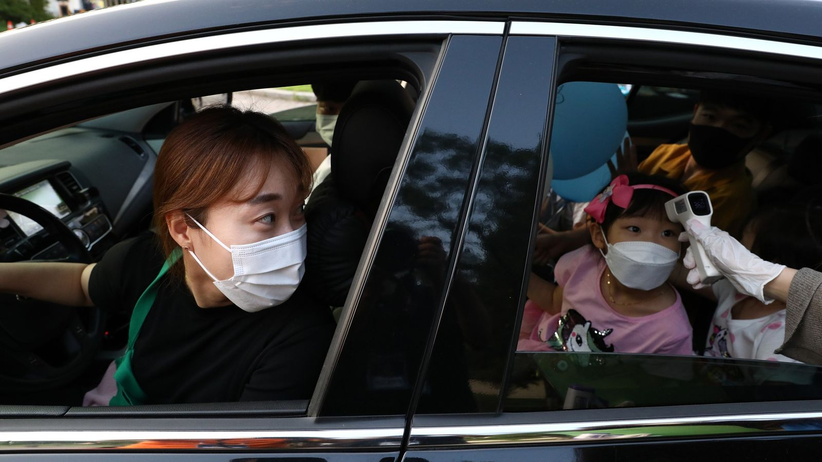 Fotografía de una madre y su hija en un covid-auto