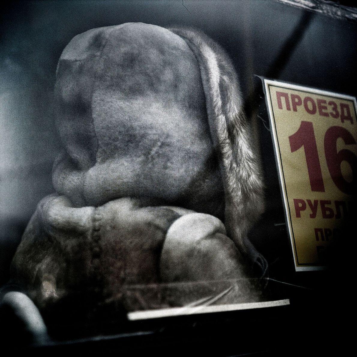 Una mujer abrigada en el interior de un autobús.
