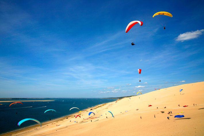 Imagen de parapentistas en la Duna de Pyla sobre la playa Corniche en La Teste De ...