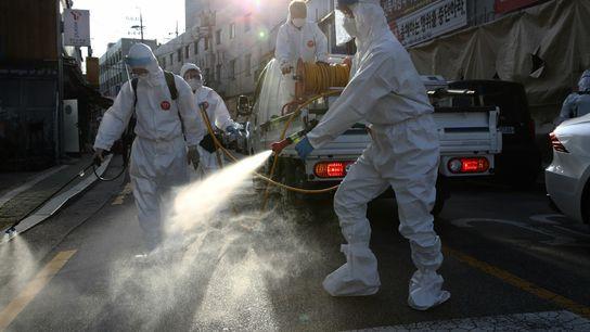 Unos trabajadores desinfectan una calle en Seúl