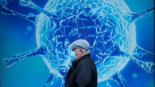 Un hombre pasa frente a una ilustración de un virus
