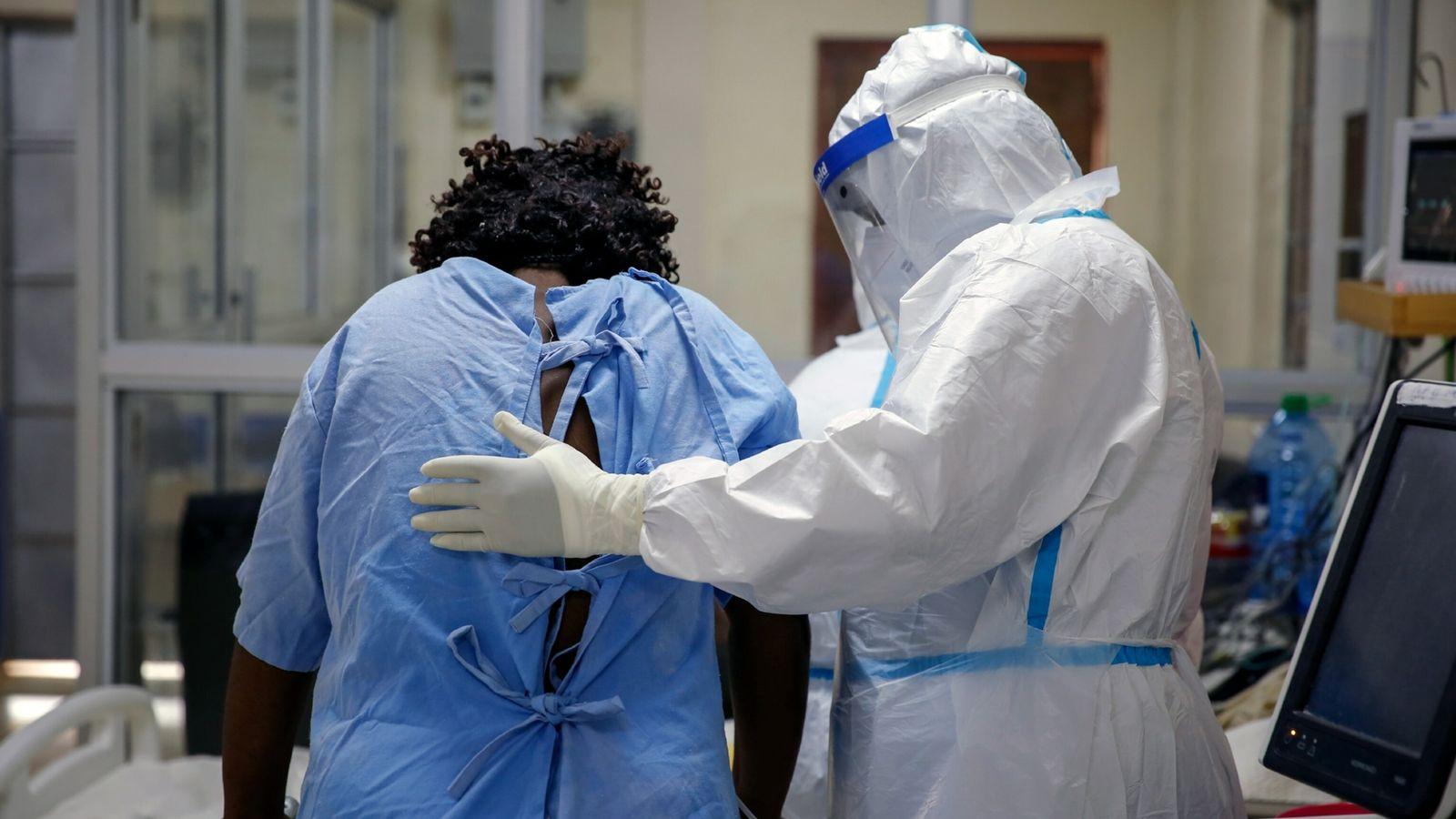 Un trabajador sanitario ayuda a un paciente de coronavirus