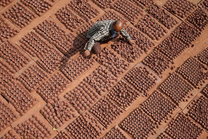 Un alfarero coloca lámparas de barro
