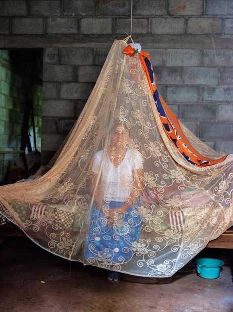 Una red antimosquitos protege a María Agustina Márquez en la casa que comparte con su marido y su nieta cerca de Intipucá. Allí, muchos dependen de los envíos de sus parientes en Estados Unidos.