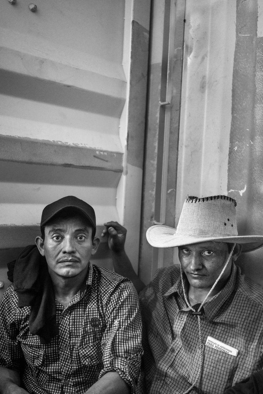 El Gulsnay, El Salvador. 31 de octubre de 2018. Dos hombres salvadoreños viajan dentro de un camión en camino a la frontera entre El Salvador y Guatemala.