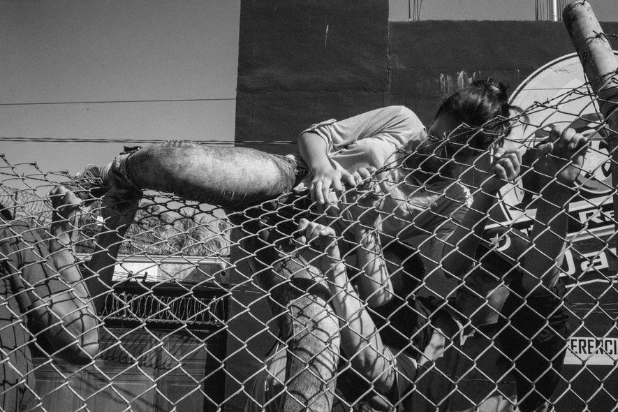 Tecún Umán, Guatemala. 2 de noviembre de 2018. Los migrantes salvadoreños intentan saltar una valla en cruce fronterizo restringido entre Guatemala y México en Tecún Umán.