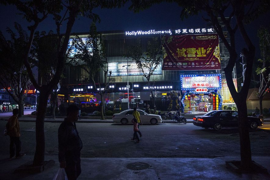 Residentes y turistas pasean frente a una sala de juegos nocturna en Mong La, un enclave semiautónomo en Birmania.