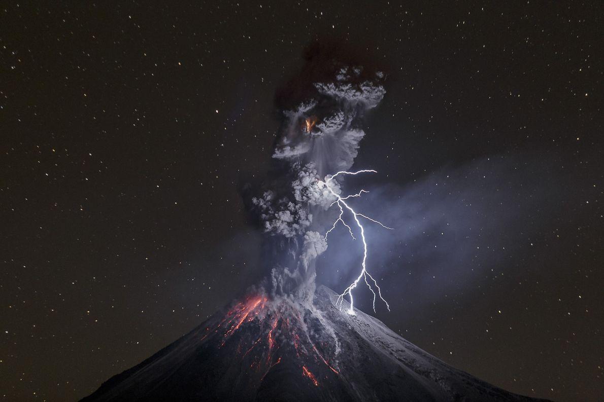 Un rayo atraviesa el cielo nocturno sobre el monte Colima mientras una columna de cenizas arremolinadas …