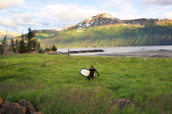 Un surfero cargando con su tabla a través del paisaje cerca de Turnagain Arm, fuera de ...