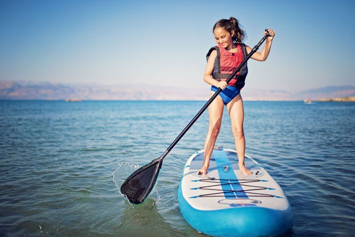 Una niña practica paddlesurf en el mar.