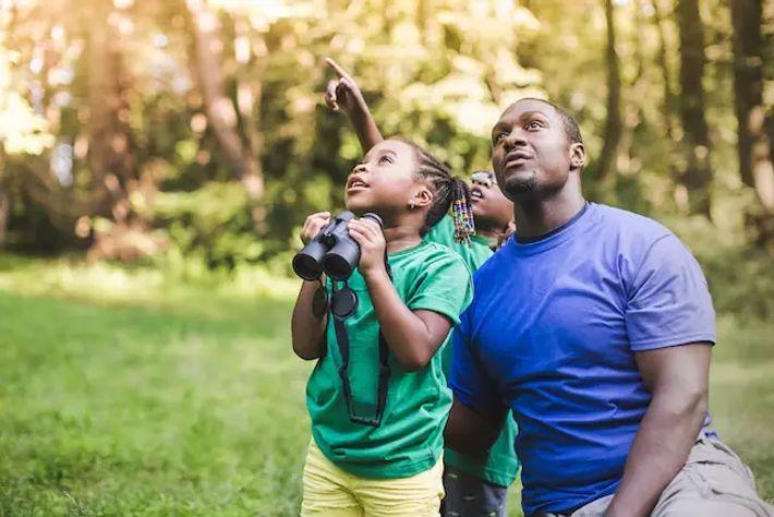 Una familia observa animales con prismáticos