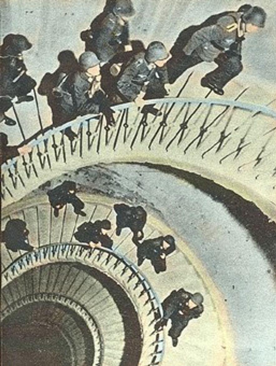 Soldados alemanes suben la escalera de caracol que lleva hasta la azotea.
