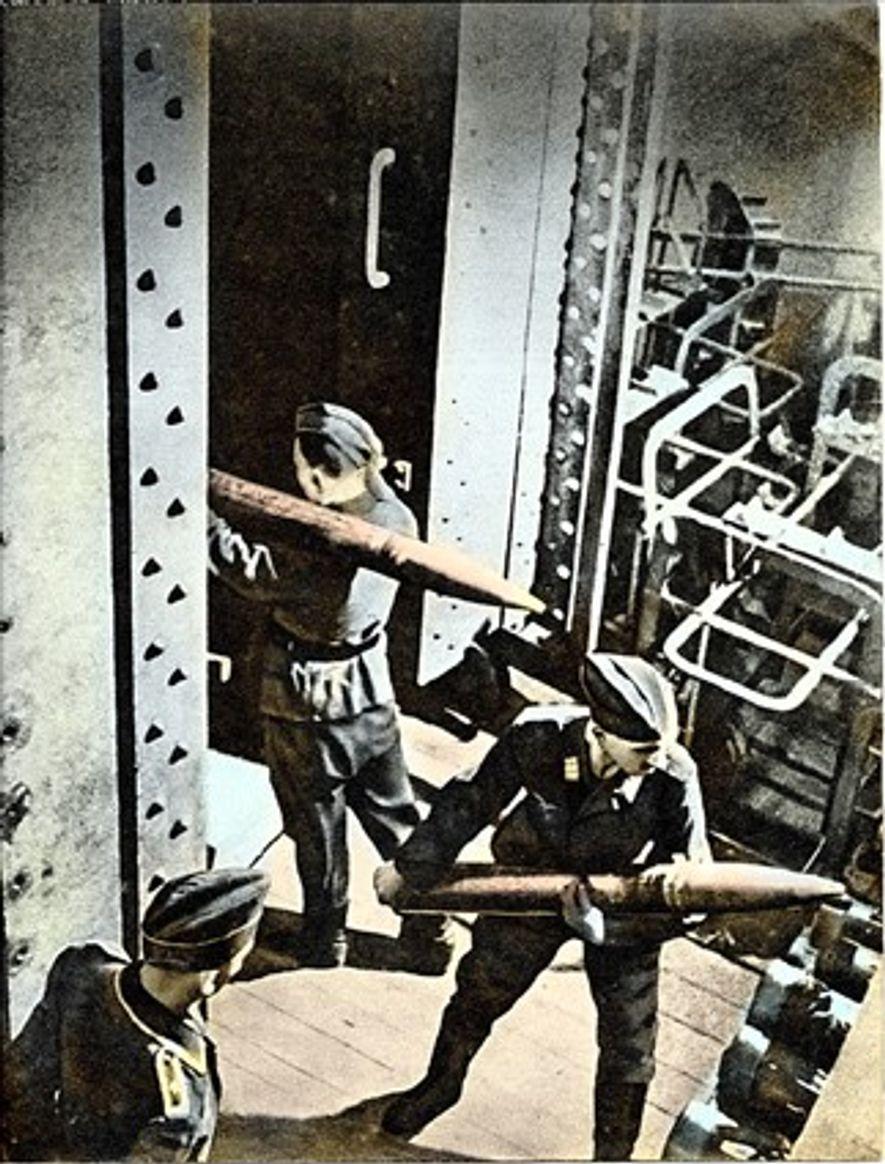 Artilleros alemanes cargan munición en el elevador blindado.