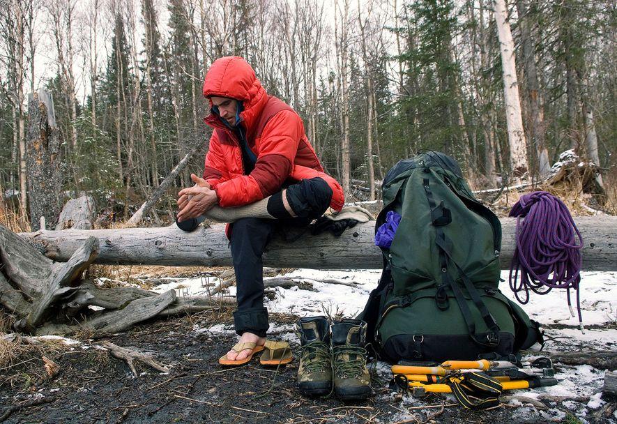 Un excursionista deja airear las ampollas de sus pies sentado en un tronco caído en Anchorage, ...