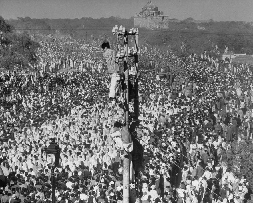 Tras el asesinato de Gandhi en 1948, unos hombres se suben a los postes telefónicos para ...