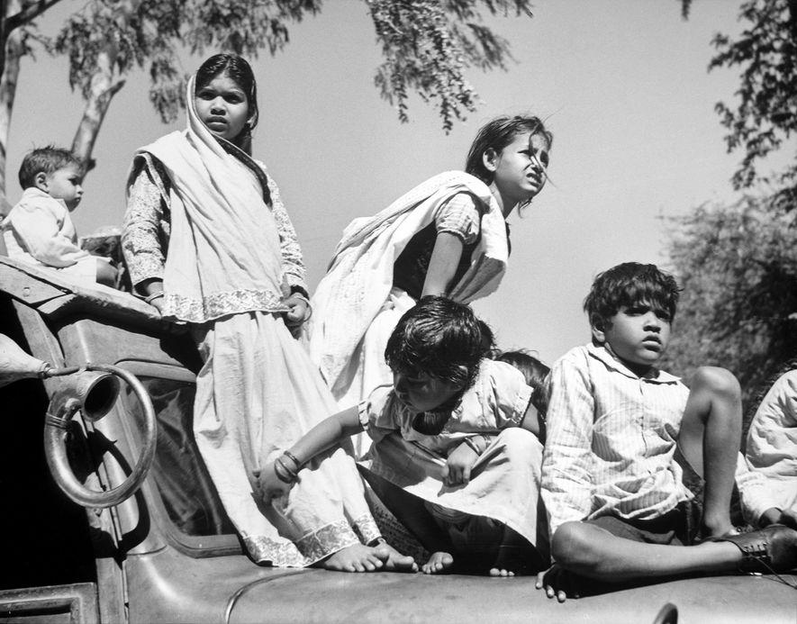 Tras el asesinato de Gandhi en 1948, unos niños se suben a los coches para ver ...
