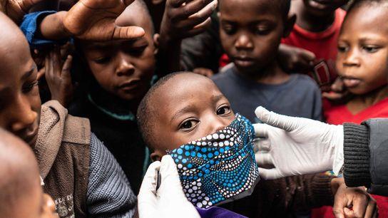 Un cooperante le pone una mascarilla a un niño