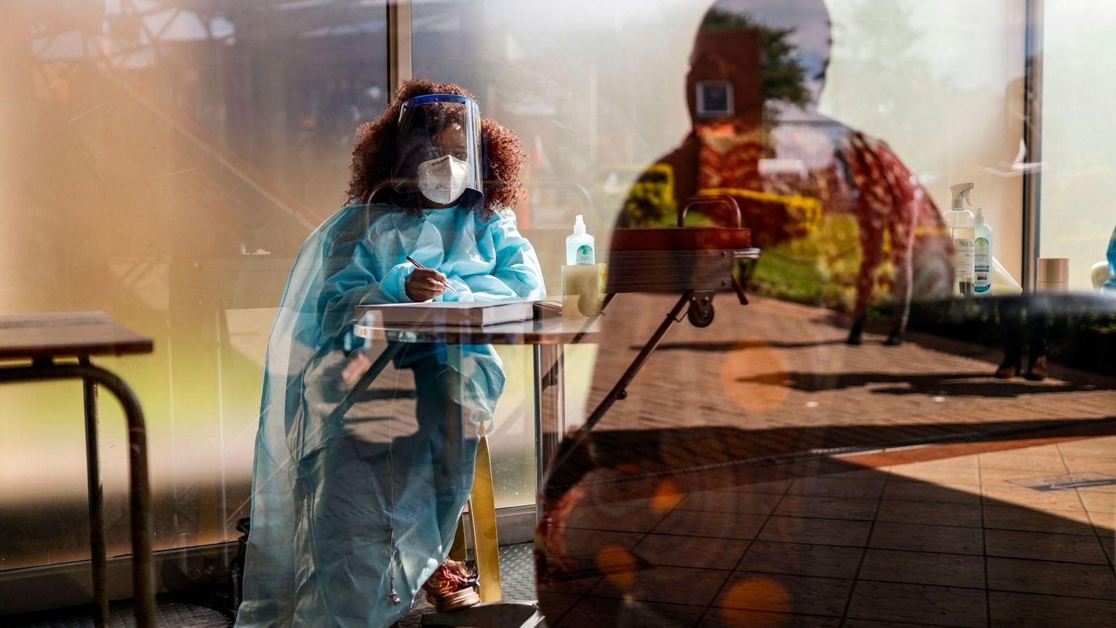 Imagen de una trabajadora sanitaria haciendo un cribado de síntomas de COVID-19
