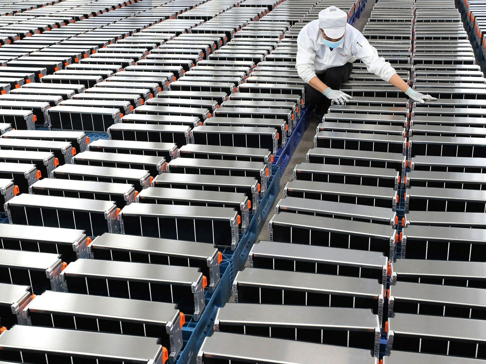 Un trabajador inspecciona las baterías de los coches