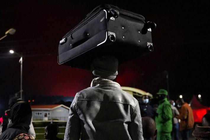 Una persona lleva una maleta en la cabeza