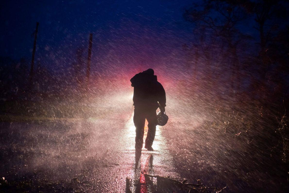 El jefe de bomberos de Montegut, Toby Henry, regresa bajo la lluvia a su camión mientras ...