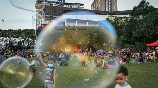 Unos niños con mascarillas juegan con burbujas en un parque