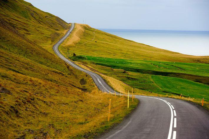Fotografía de una carretera frente a un fiordo cerca de Siglufjörður