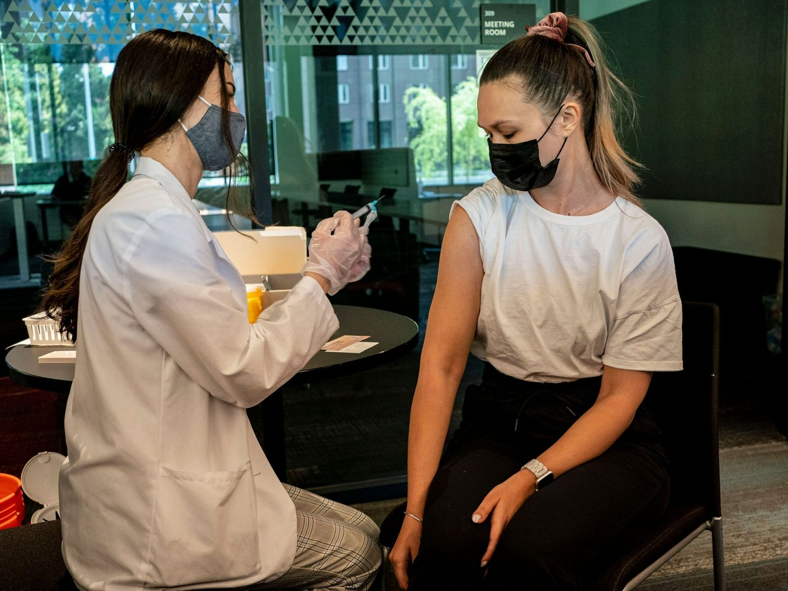 Una estudiante recibe una vacuna contra la COVID