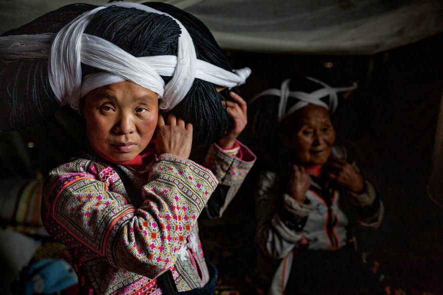 Las mujeres de la tribu Longhorn Miao de la provincia de Guizhou llevan tocados elaborados de ...